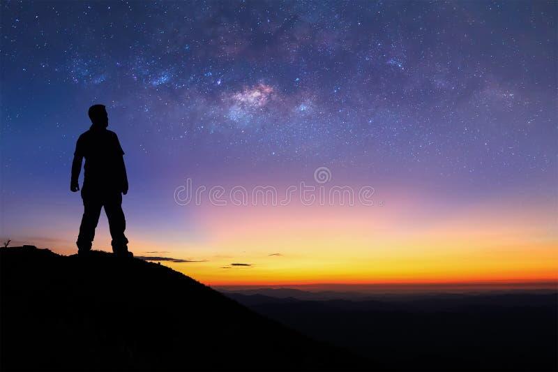 Konturn av mannen står överst av berget och tycker om till se royaltyfria foton