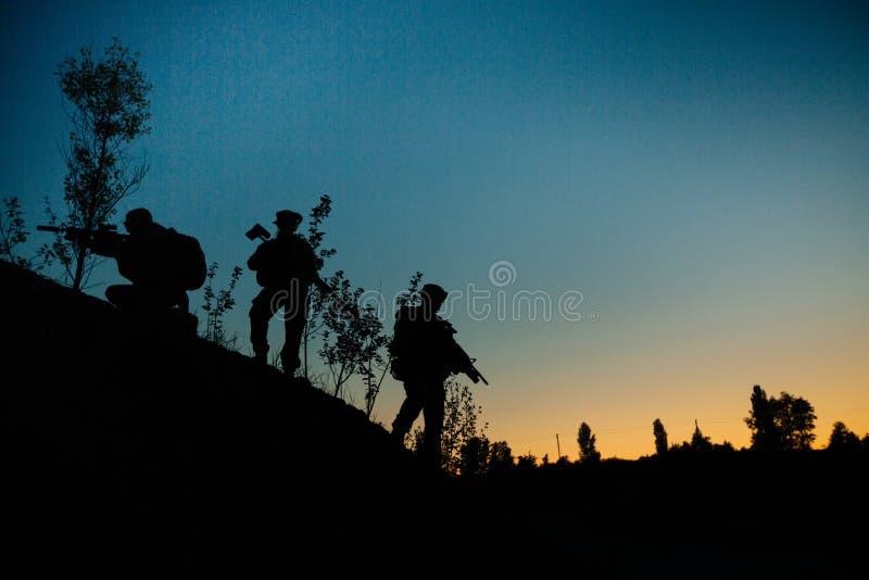 Konturn av militären tjäna som soldat med vapen på natten skott hol royaltyfria foton
