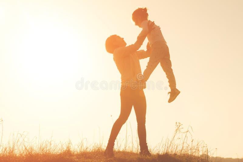 Konturn av smilling av den unga modern som kastar upp, behandla som ett barn i himlen på solnedgången arkivfoto