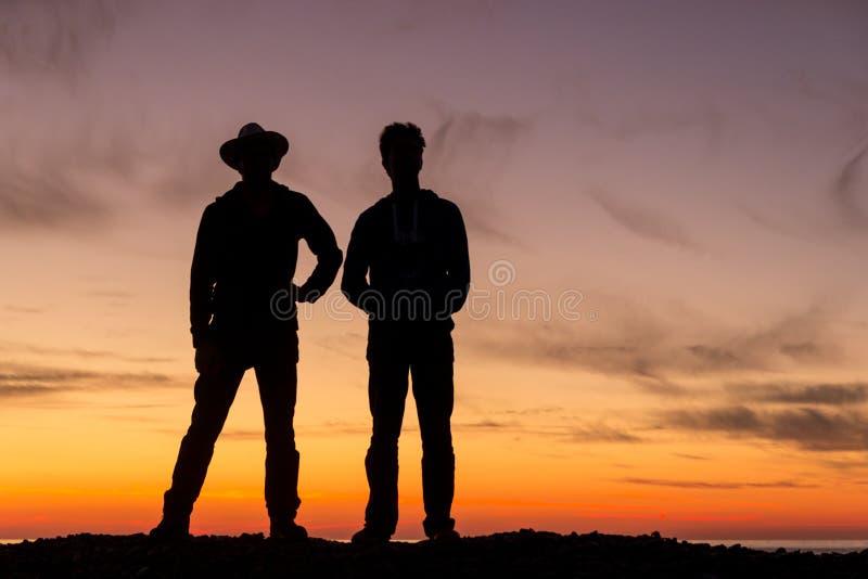 Konturn av två unga män som är roterande tillbaka till en härlig solnedgång royaltyfri foto