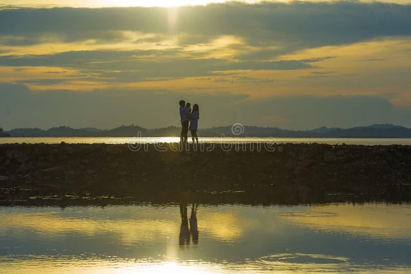 Konturn av unga romantiska par som rymmer och spelar med sonen eller dottern behandla som ett barn lite, tycka om solnedgången so arkivbilder