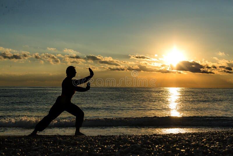 Konturn av vanor för en man påskyndar chun på stranden arkivfoto