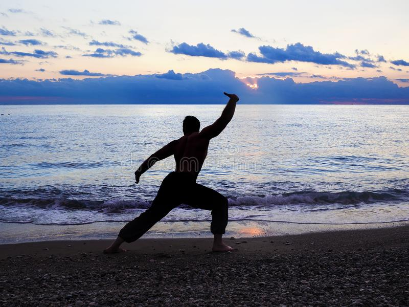 Konturn av vanor för en man påskyndar chun på stranden fotografering för bildbyråer