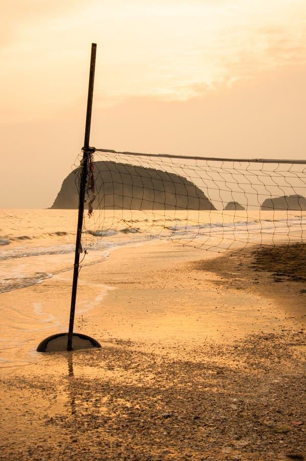 Konturn av volleyboll förtjänar på en strand på soluppgång. royaltyfria bilder
