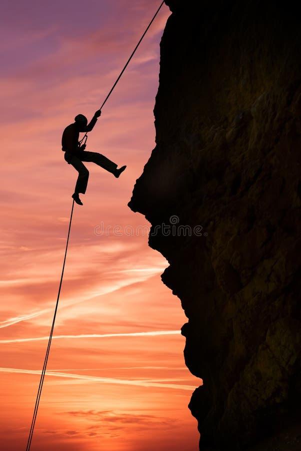 Konturn av ytterligheten vaggar klättraren mot härlig solnedgång royaltyfria foton