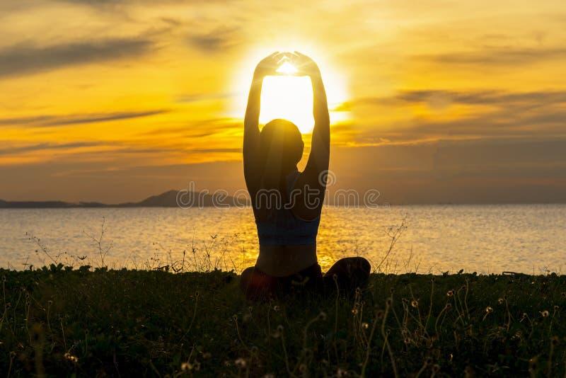 Konturn för kvinnan för meditationyogalivsstilen på havssolnedgången, kopplar av livsviktigt royaltyfria bilder