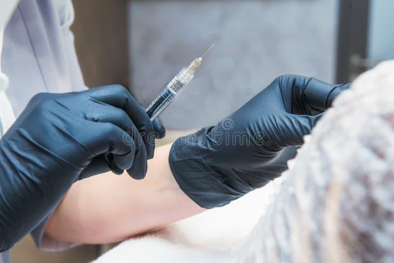 Konturowy klingeryt: Dermatolog lekarka wstrzykuje napełniacz Zakończenie w górę żeńskich ręk robi zastrzykowi w wargach cosmetol fotografia royalty free