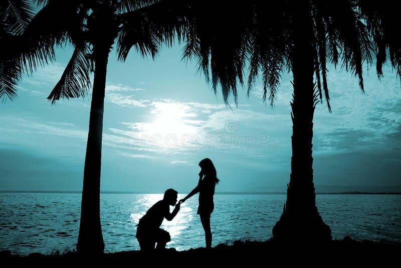 Konturpar, kvinnaställningen och mannen sitter på golvet, föreslår hållen och att kyssa hennes hand för henne till att gifta sig  arkivfoton
