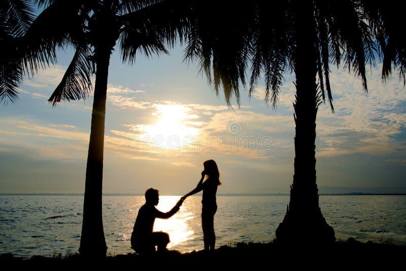 Konturpar, kvinnaställningen och mannen sitter på golvet och rymmer hennes hand för föreslår henne till att gifta sig arkivbild