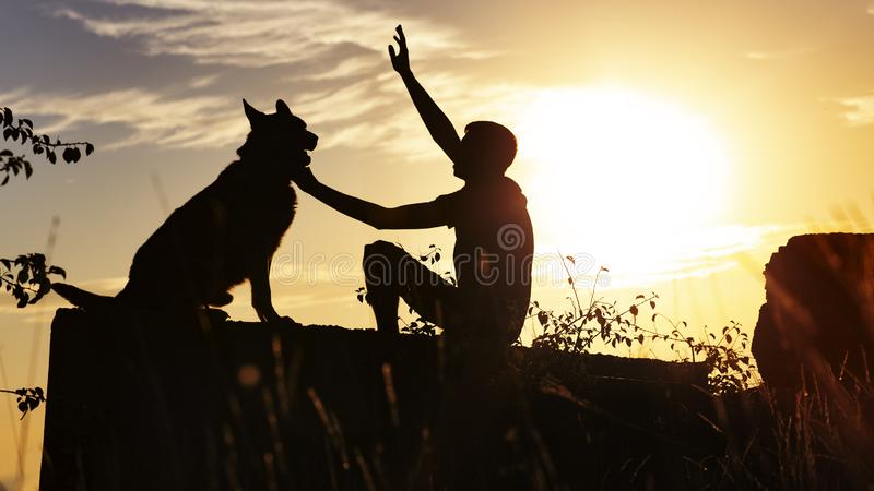 Konturprofil av mannen och hunden mot horisonten av den molniga himlen, tysk herde för pojkedrev som sitter på en konkret tjock s fotografering för bildbyråer