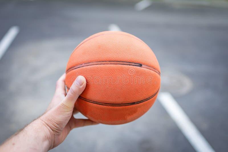 Kontursikt av en boll för korg för innehav för basketspelare arkivbild