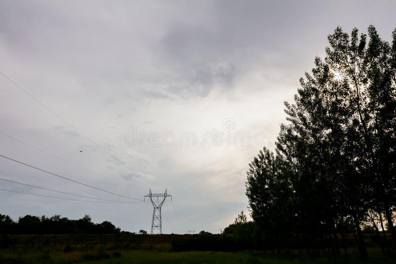 Kontursikt på elströmlinje, träd och molnig himmel på arkivbild
