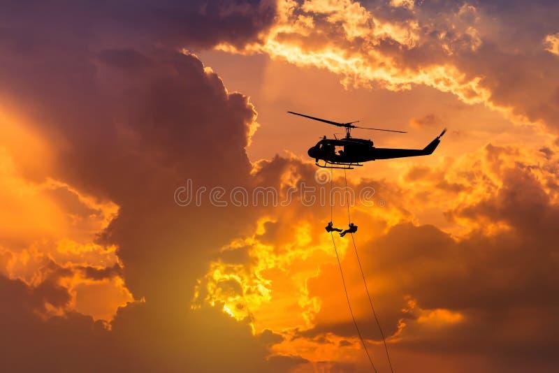 Kontursoldater i handling som rappelling, klättrar ner från helikoptern med räknareterrorism för militär beskickning på solnedgån royaltyfria bilder