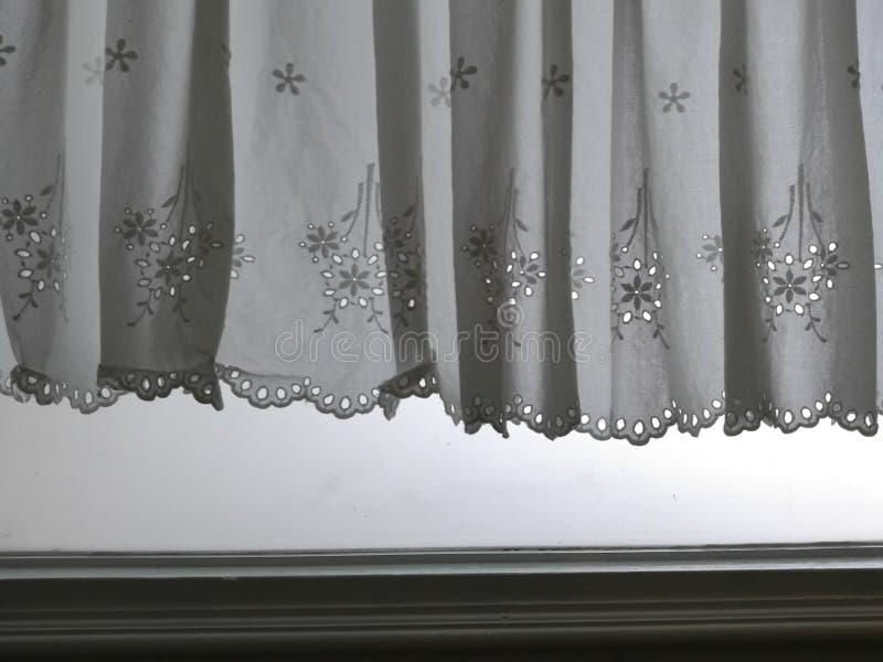 Konturvit snör åt satänggardinen som hänger på fönster ovanför fönsterjamp med semitransparent behind för solljus, garneringinre arkivfoton