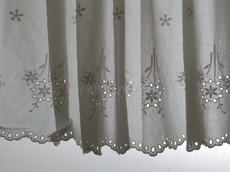 Konturvit snör åt satänggardinen som hänger på fönstret med semitransparent behind för solljus, inre rum för garnering arkivbild