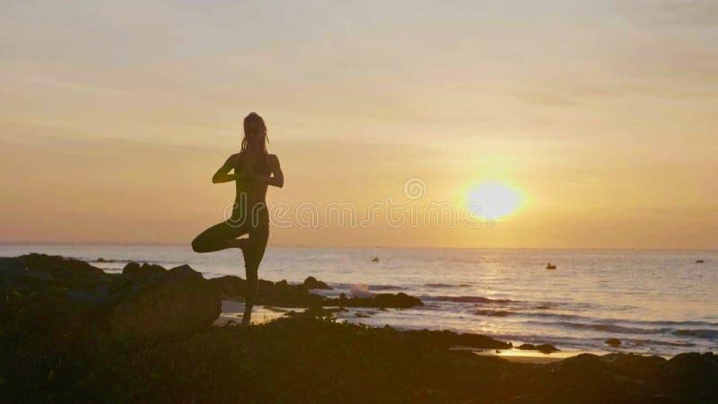 Konturyogaövning på solnedgången Yong kvinna som gör yogaövning på stranden royaltyfri bild