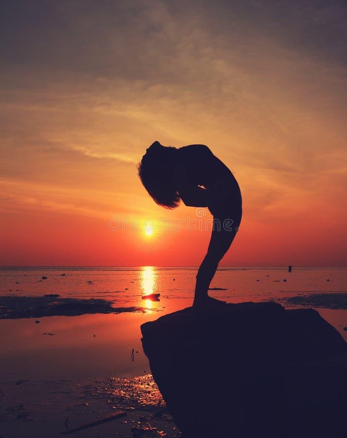Konturyogaflickan vid stranden på soluppgång som gör att stå, poserar fotografering för bildbyråer