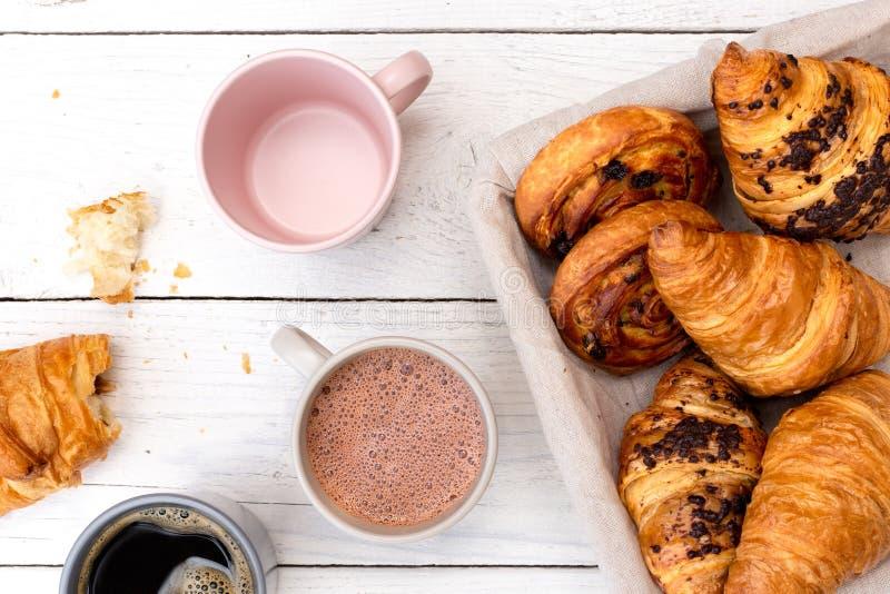 Kontynentalny śniadanie z gorącą czekoladą, czarną kawą i koszem ciasta, Połówka jedząca na białym drewnie z góry obraz royalty free