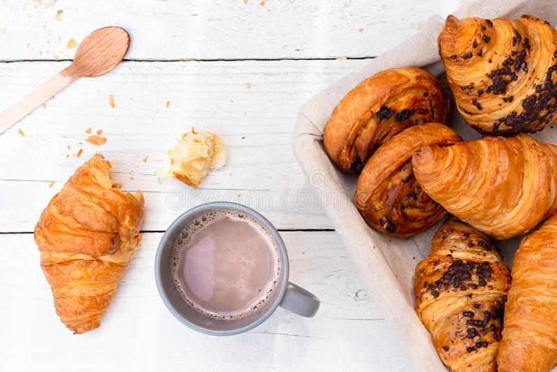Kontynentalny śniadanie z gorącą czekoladą i koszem ciasta Połówka jedząca na białym drewnie z góry zdjęcie royalty free