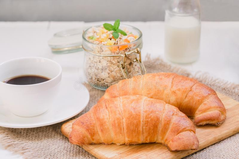 Kontynentalny tradycyjny śniadaniowy Croissant, filiżanka kawy i granola, Na białym tle na brezentowej pielusze, fotografia royalty free