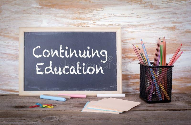 Kontynuować edukacja tekst na blackboard Stary drewniany stół z teksturą obraz royalty free