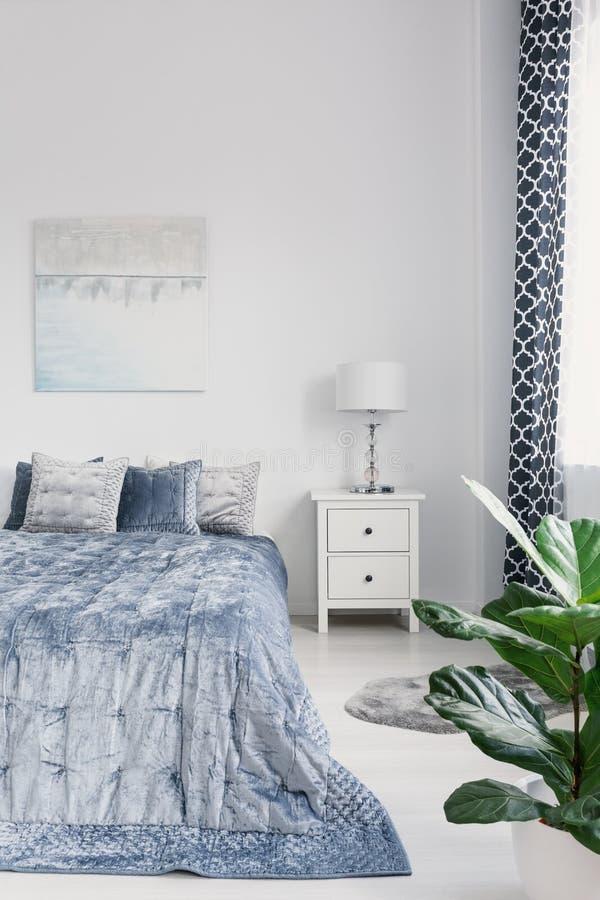 Konungformatsäng med elegant blå sängkläder, vit nightstand med lampan och målning på väggen i den lyxiga sovruminre, verklig pho arkivfoton