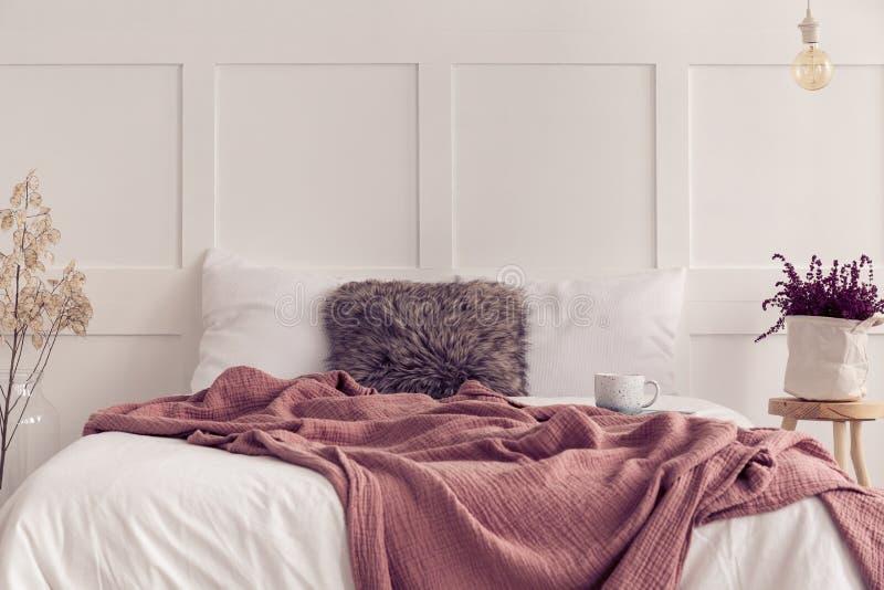 Konungformatsäng med vit sängkläder och smutsig rosa filt, verkligt foto med kopieringsutrymme royaltyfri bild