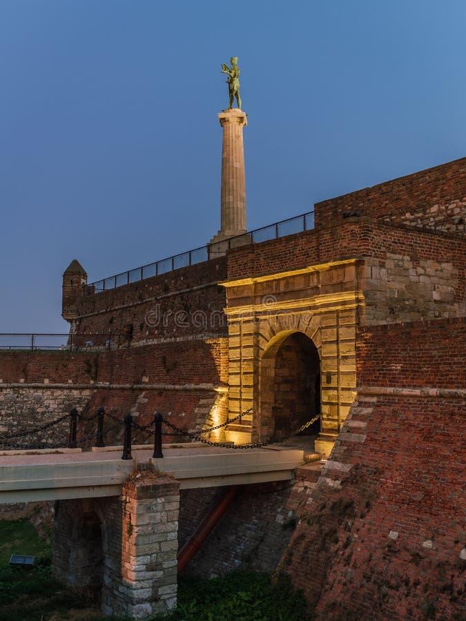 Konungport i Kalemegdan, Belgrade, Serbien, med segrarestatyn i bakgrund på natten arkivfoto