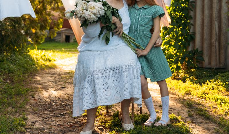 Konversation mellan farmodern och sondottern farmor äldre kvinna som sitter och kramar hennes sondotter, flicka och hol royaltyfria bilder