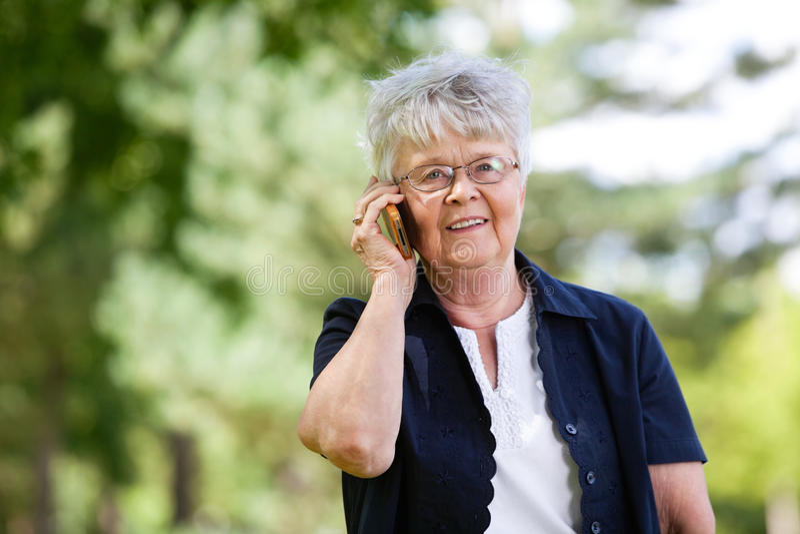 konversation som har den mobila telefonpensionärkvinnan royaltyfri bild
