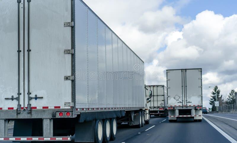 Konvooi van grote installatie semi vrachtwagens met semi aanhangwagens die op de brede weg op verscheidene lijnen lopen stock fotografie
