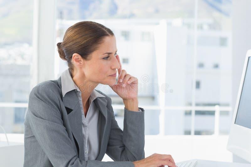 Konzentratgeschäftsfrau, die Computer verwendet lizenzfreie stockfotografie