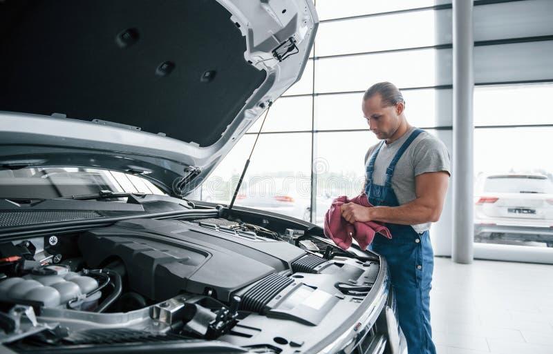 Konzentration am Arbeitsplatz Mann in blauer Uniform arbeitet mit kaputtem Auto Reparaturen lizenzfreie stockbilder