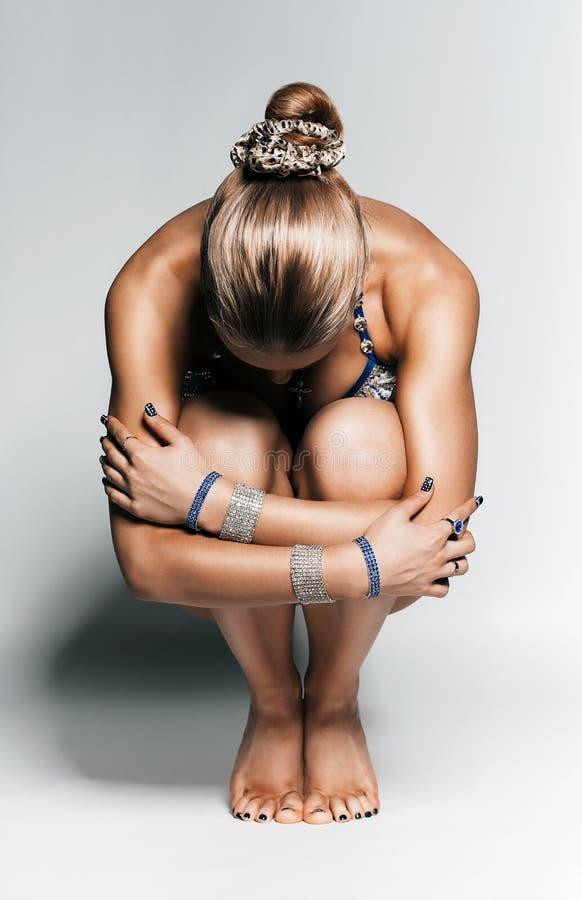 Konzentration des Sitzens der sportlichen Frau auf dem Boden stockbilder