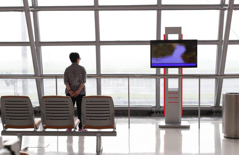 Konzentrieren Sie sich auf die Rückenlehneansicht der Frau stehend nahe dem Fenster O stockfotos