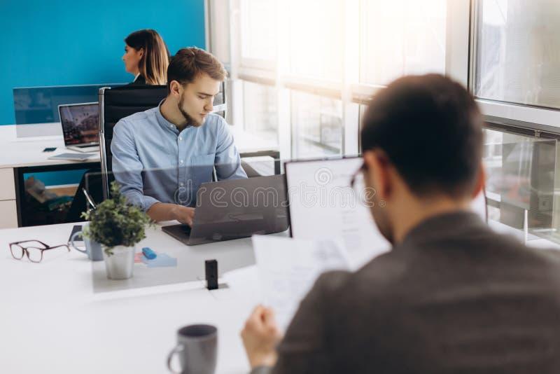 Konzentriert auf Arbeit Starker junger Bartmann, der an Laptop beim Sitzen an seinem Arbeitsplatz im Büro arbeitet stockbilder