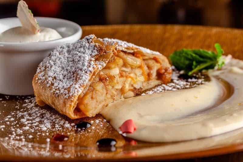Konzept der österreichischen Küche ApfelkuchenBlätterteig Strudel mit Äpfeln und Zimt Servierteller im Restaurant lizenzfreies stockfoto