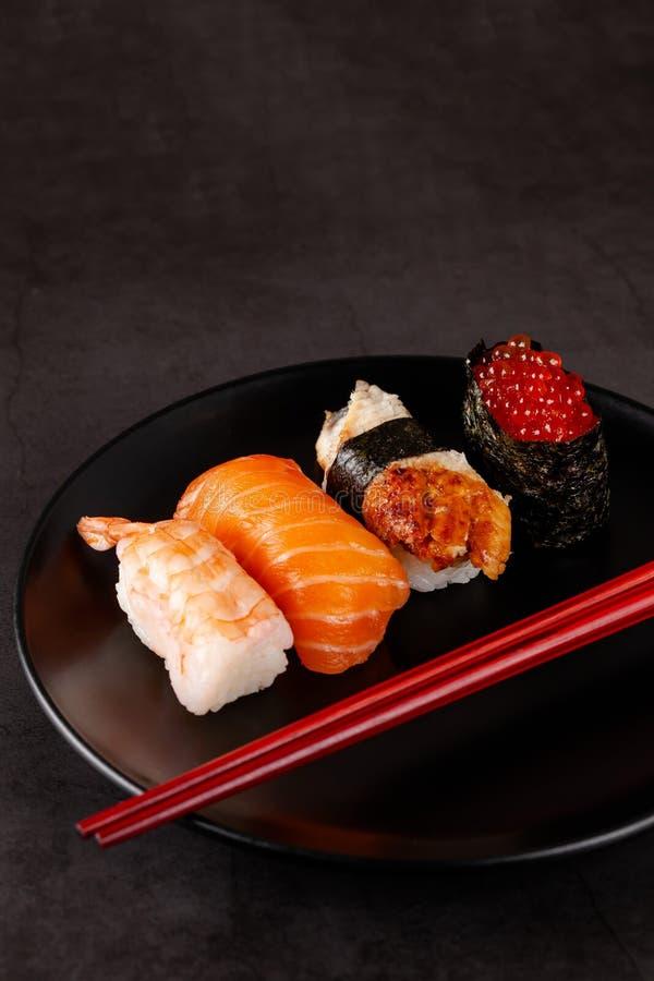 Konzept der asiatischen Küche Japanische Sushi mit Sojasoße auf einem Schwarzblech, auf einem schwarzen Hintergrund Rote chinesis lizenzfreies stockbild