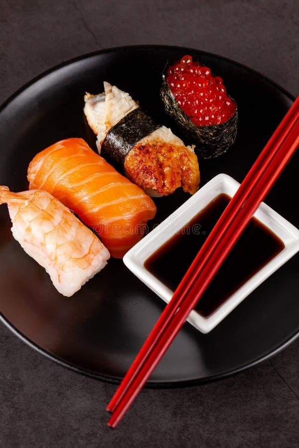 Konzept der asiatischen Küche Japanische Sushi mit Sojasoße auf einem Schwarzblech, auf einem schwarzen Hintergrund Rote chinesis lizenzfreie stockfotos