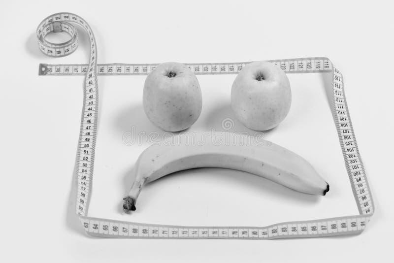 Konzept der Diät und der Gesundheit Fruchtgesicht mit traurigem Ausdruck gestaltet mit messendem Band lizenzfreie stockbilder
