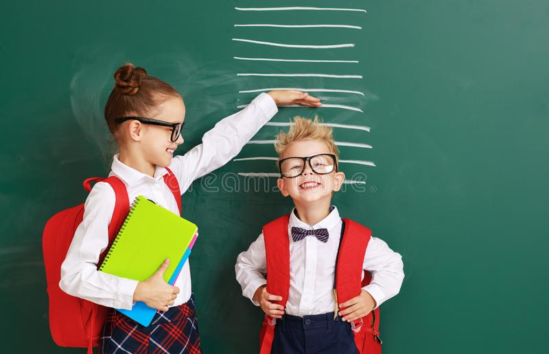 Konzept der Entwicklung in der Ausbildung Kinder Junge und Studentinnen messen Wachstum über Schultafel lizenzfreies stockfoto