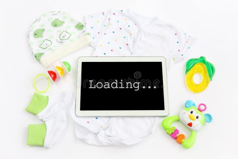 Konzept der Erweiterungsfamilie und der Erwartung für Baby: sortieren Sie Tablette mit Aufschriftladen, Kleidung für neugeborenes lizenzfreie stockfotografie