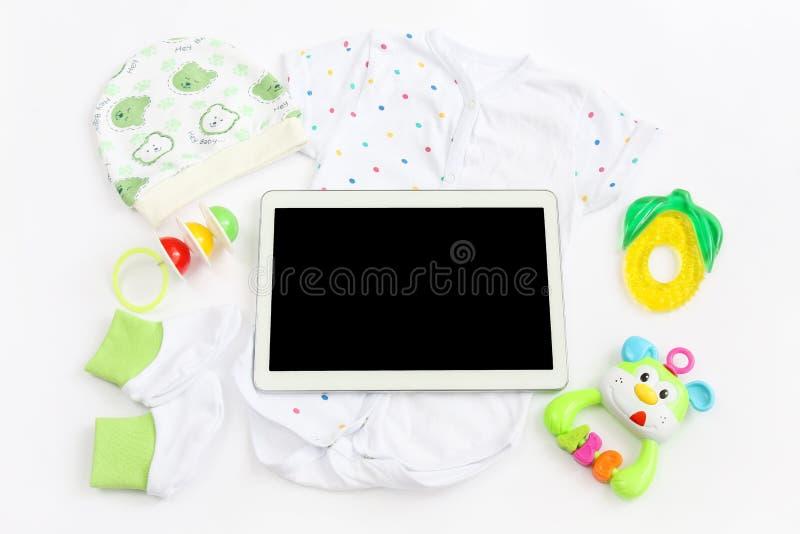 Konzept der Erweiterungsfamilie und der Erwartung für Baby: Tablette des leeren Bildschirms, Kleidung für neugeborenes - kopierte lizenzfreie stockbilder