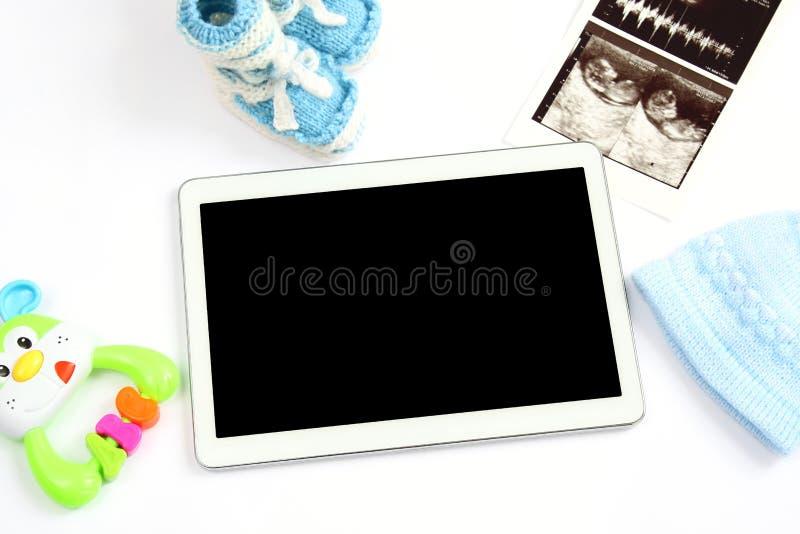 Konzept der Erweiterungsfamilie und der Erwartung für Baby: Tablette des leeren Bildschirms, Ultraschallscan des Babys, Kleidung  lizenzfreie stockfotos