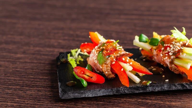 Konzept der europäischen Küche o Rohe Kalbfleischrolle mit knusperigem Gemüse, Gurke, Sellerie, roter grüner Pfeffer stockbild