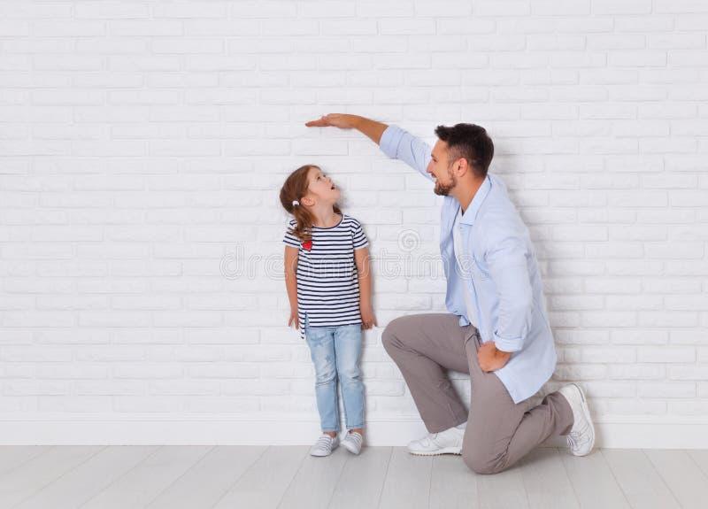 Konzept der Familie der Vater misst Wachstum des Kindes nach DA lizenzfreies stockfoto