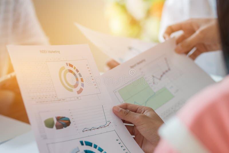 Konzept der gemeinsamen Sitzung der Arbeitsgruppen: Geschäftsleute, die zusammen mit im Büro befindlichen Dokumenten-Graphen-Papi stockfotos