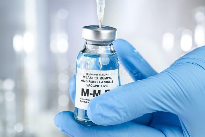 Konzept der Gesundheitsfürsorge mit einer Hand in medizinischen Handschuhen mit MMR, Masern, Mumps und Röteln, Durchstechflasche  lizenzfreie stockfotografie