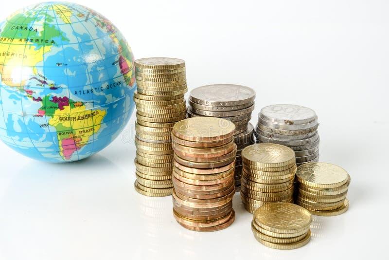 Konzept der globalen Wirtschaft mit Bereichkugel und von den Münzen über Weiß gestapelt lizenzfreies stockbild