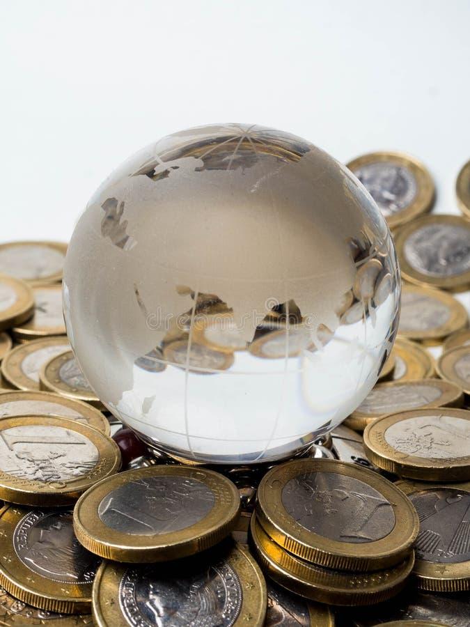 Konzept der globalen Wirtschaft mit Bereichkugel und von den Münzen über Weiß gestapelt lizenzfreie stockbilder